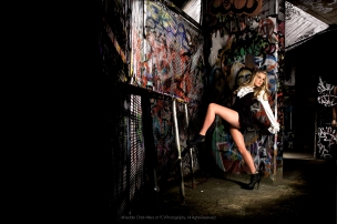 female model posing by graffiti covered wall