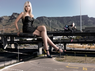 Giant female model sitting on bridge close to Table Mountain in Cape Town