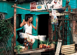 Female model with chicken by spaza shop in African Township Elle Magazine