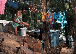 Female model cleaning clothes in African Township Elle Magazine