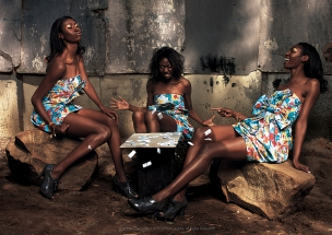 Female models playing dice game in African Township Elle Magazine