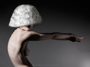 Dark shot of nude female model with wig in studio
