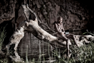 Young himba girl sitting on tree hanging over hot spring